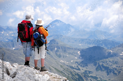 Male and female hikers shoot from the back standing looking at mountain view at Vihren summit, Pirin, Bansko, Bulgaria, woman is pointing with a pole at Kamenica summit