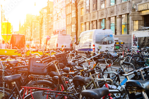 Bicycles parked on the city street in rays of the sun in Amsterd Wallpaper Mural