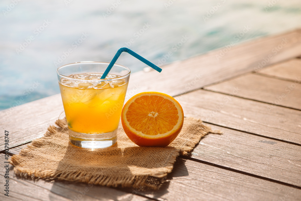 Fototapeta Close up of screwdriver cocktail alcohol drink with orange juice, slices and ice standing near the pool. Refreshing iced lemonade beverage in glass by the poolside. Sun glares. Background, copy space.