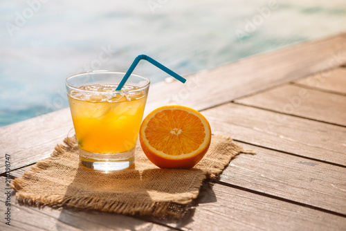 Fototapeta Close up of screwdriver cocktail alcohol drink with orange juice, slices and ice standing near the pool. Refreshing iced lemonade beverage in glass by the poolside. Sun glares. Background, copy space. obraz