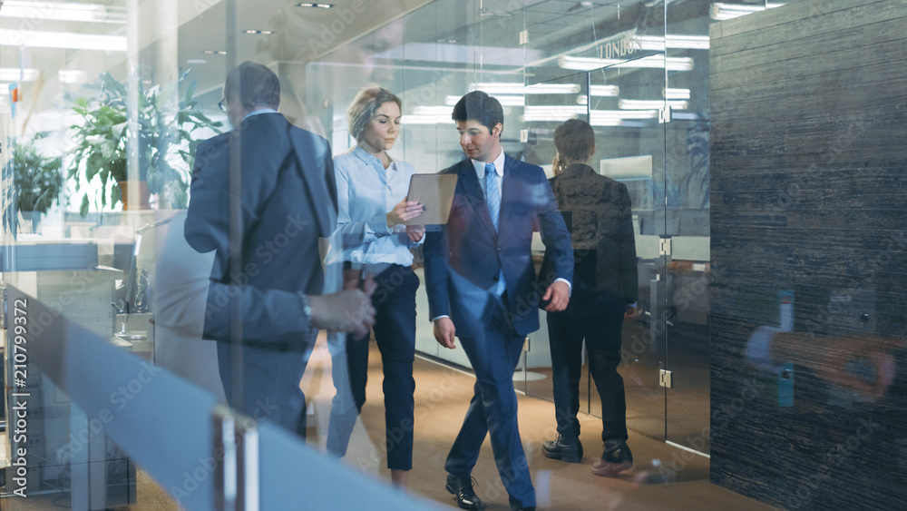 Fototapeta Businessman and Businesswoman Walking Through Glass Hallway, Discussing Work and Using Tablet Computer. Busy Corporate Office Building with Many Workers.