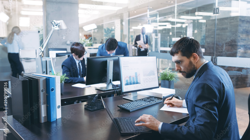 Fototapeta Professional Businessman Works on His Desktop Computer, Uses Laptop. In the Background Busy Office with Diverse Group of Business People.  Modern Glass and Marble Corporate Building.