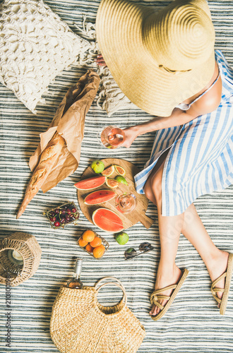 Keuken foto achterwand Summer picnic setting. Woman in linen striped dress and straw sunhat with glass of rose wine in hand, fresh fruit and baguette on blanket, top view. Outdoor gathering or lunch