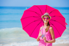 Girl With A Pink Umbrella On The Sandy Beach