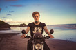 tattooed man sitting on motorbike on ocean beach and looking at camera