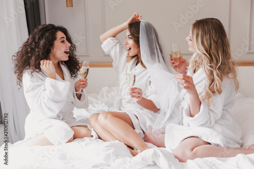 Photo Portrait of pretty three women 20s celebrating bachelorette party and drinking g