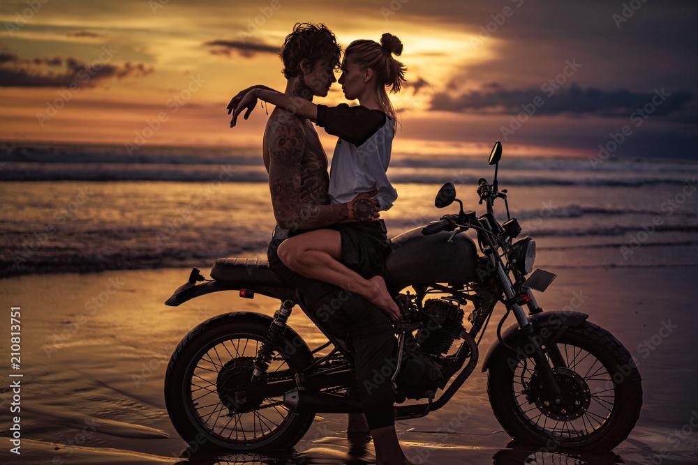 namiętna para przytulanie na motocyklu na plaży podczas zachodu słońca <span>plik: #210813751 | autor: LIGHTFIELD STUDIOS</span>