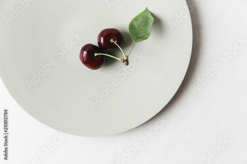 Cherries on a plate on a white surface. - 210813784