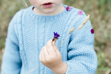 Little Girl Wearing A Blue Knitted Jumper Showing A Bunch Of Tiny Little Purple Flowers.