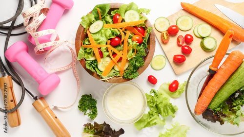 Tuinposter Groenten Mixed vegetables salad with cream and fitness equipments on white background.