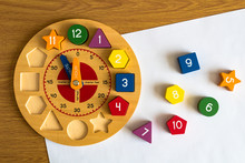 Toy Wooden Clock On A Sheet Of...