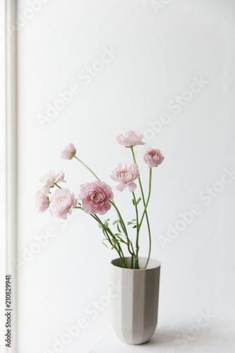 Pink ranunculus in a grey design vase near an bright window.