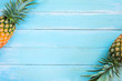 Tropical pineapple on wood plank blue color. frame layout summer vacation background concept.