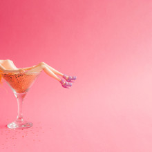 Doll Bathing In Martini Glass Full Of Gold Glitter On Pink Background. Creative Minimal Beauty Summer Concept