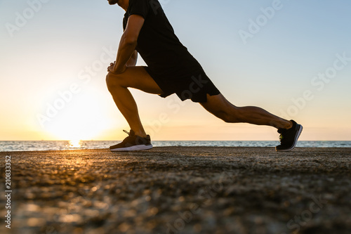 Canvas Print cropped shot of sportsman doing lunges during training on seashore