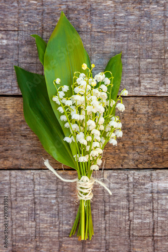 Papiers peints Narcisse Bouquet of flowers beautiful smell lily of the valley or may-lily on rustic old vintage wooden background, top view flat lay. Garden in spring or summer concept