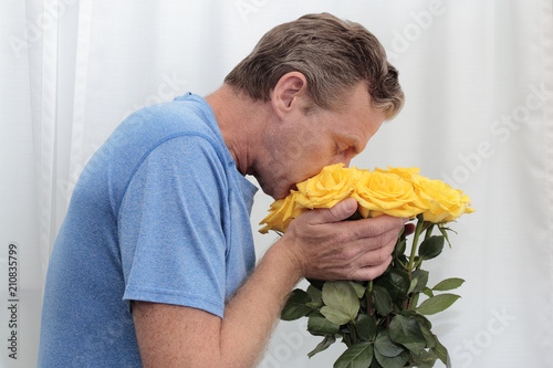 Mature man with his face in a yellow roses bunch.