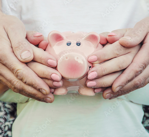 Fotografía The child and parents are holding a piggy bank in their hands