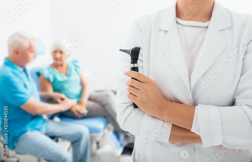smiling doctor standing before elderly patients in medical office Canvas Print
