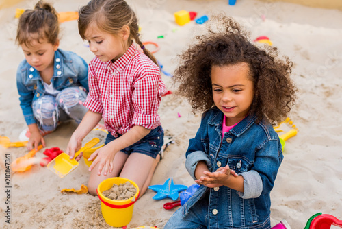 selective focus of curly african american child playing wit friends in sandbox a Canvas Print