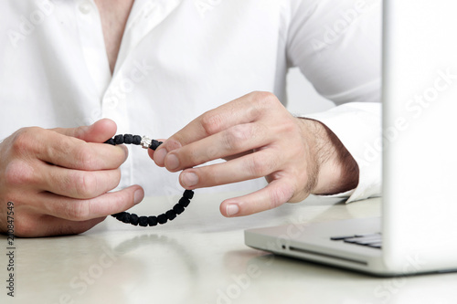 Businessman holding prayer bracelet in the office, hope and waiting concept