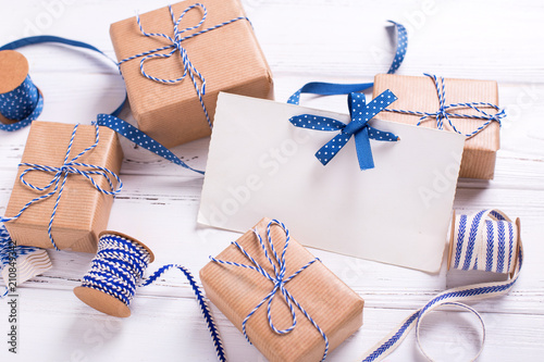 Empty tag and wrapped gift boxes with presents and blue ribbon