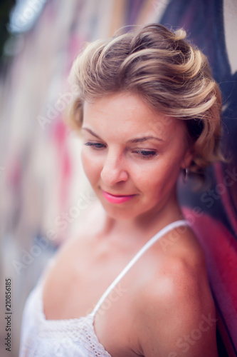 Portrait of beautiful woman posing on colorful wall background outdoors Poster