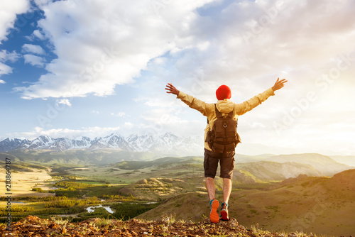 Foto  Happy tourist man raised arms against sunset mountains