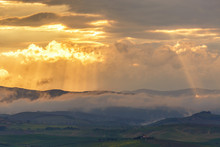 Sunset Over The Mountains With Sun Rays And Low Clouds