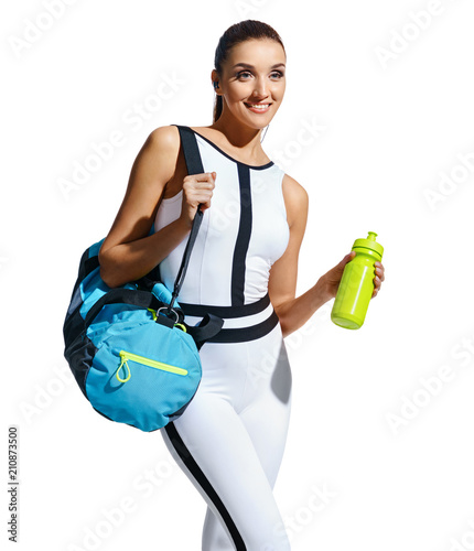 Photo Go to gym! Smiling sporty woman in fashionable sportswear with sports bag and shaker on white background