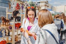 Two Girls Friends Choosing A Cutting Board In The Outdoor Flea Handmade Market