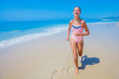 Girl in swimsuit runing and having fun on tropical beach