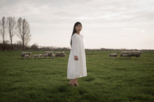 Girl Standing In Field With Sheep