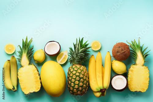 swieze-organicznie-zolte-owoc-nad-blekitnym-tlem-monochromatyczny-pojecie-z-bananem-koksem-ananasem-cytryna-melonem