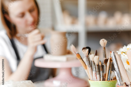 Slika na platnu A woman artist in working apron smiles and paints a clay pottery among brushes a