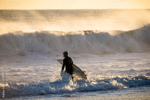 Surfer walking in sea at sunset