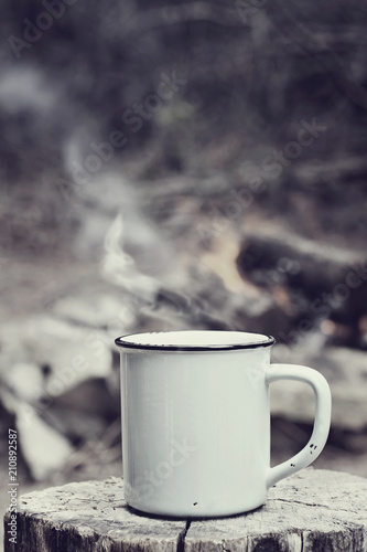 Poster Camping Cup of hot steaming coffee sitting on an old log by an outdoor campfire with a vintage antique edit. Extreme shallow depth of field with selective focus on mug.