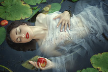 Beautiful Mermaid Girl In A White Dress In A Swamp With Water Lilies