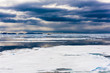 Cloudy sky and Ice pieces on the water in Arctic