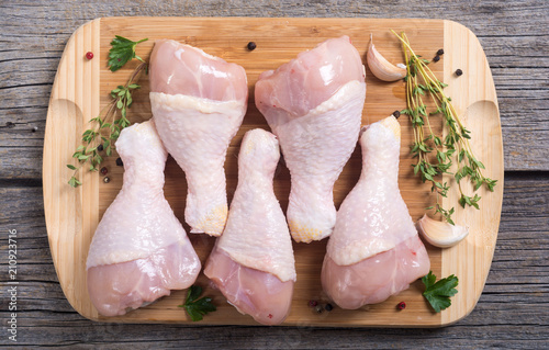 Photo Raw chicken legs with spices on cutting board
