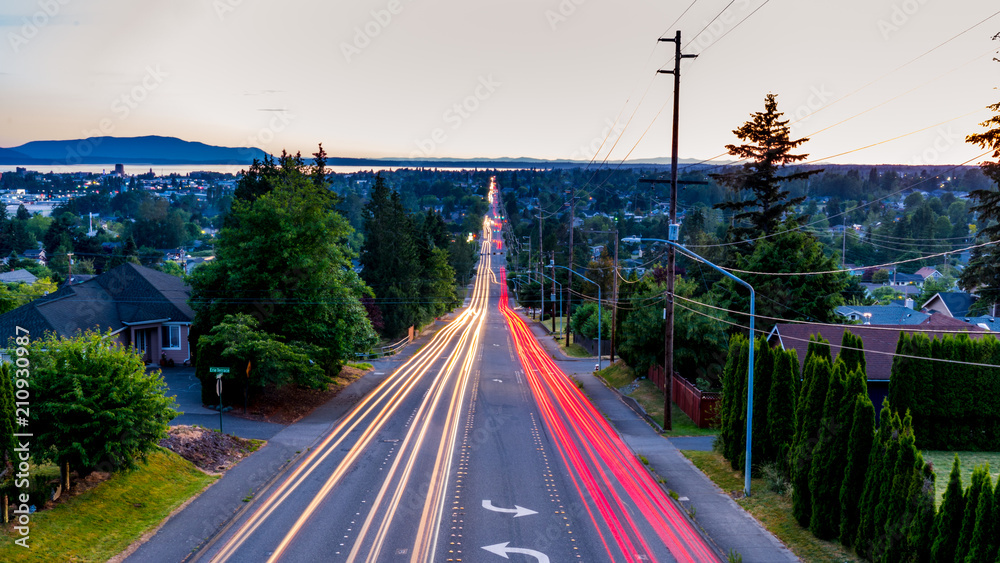 Fototapety, obrazy: View from above the city. Long exposure of Bellingham, Whatcom County.Cars trail lights and a sublime view of the Pacific ocean in the background.