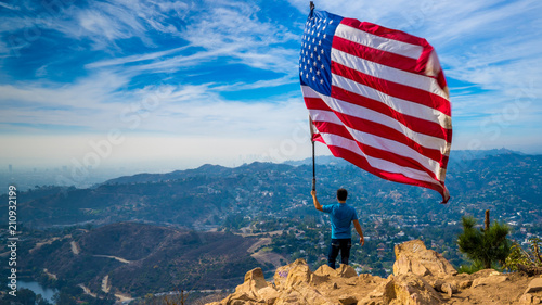Photo  Man waves American flag above Los Angeles at Hollywood Sign