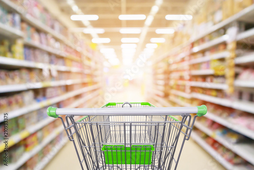 Photo Supermarket aisle product shelves interior blur background with empty shopping c