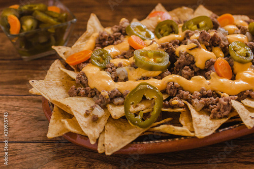 Fotografía  nacho chips corn garnished with ground beef, melted cheese, jalapeños peppers in