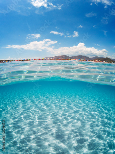Half underwater turquoise sea on summer day with a crowded beach