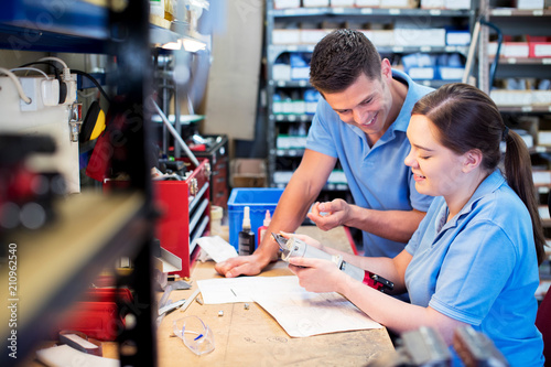 Photo Engineer And Apprentice Examining Component At Workbench