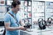 Wonderful headphones. Cheerful friendly smiling man looking at the wonderful black headphones before buying them