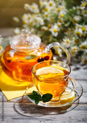 Foto op Plexiglas Thee Cup with hot tea with mint and a thyme on a wooden table in a summer garden.