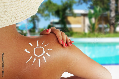 Back view of a beautiful woman taking care about her skin at swimming pool, sun protection concept