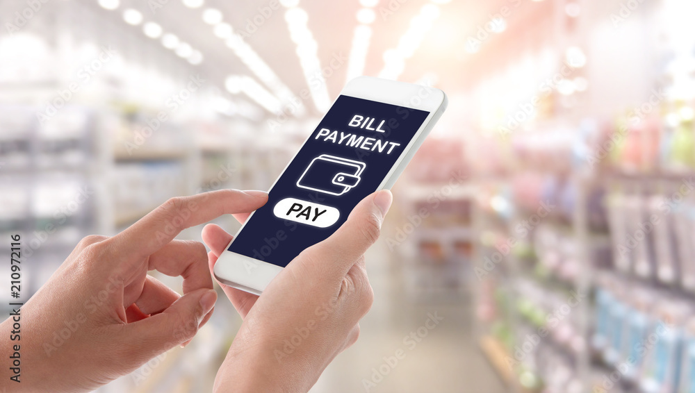 Fototapeta Woman hands holding and using smartphone with bill payment screen on blurred shopping mall interior background. Ecommerce concept.